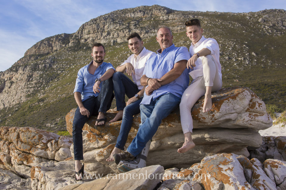 father & sons sitting on a rock