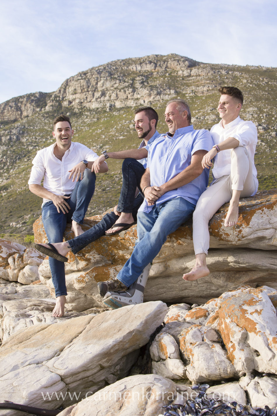 father and sons sitting on a rock